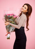 Beautiful woman with large bouquet of roses — Stock Photo