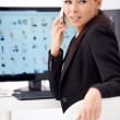 Royalty-Free Stock Photo: Business woman talking phone while sitting in front of computer