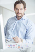 Handsome businessman sitting at the desk — Stock Photo