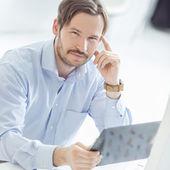Empresario joven hansome sentado en el escritorio — Foto de Stock