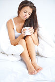 Woman drinking a cup of coffee in bed — Stock Photo