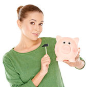 Woman testing her piggy bank with a mallet — Stock Photo