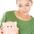 Woman giving her piggy bank a speculative look — Stock Photo