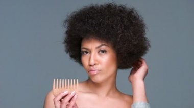 African American woman comb through her frizzy afro hairstyle — Stock Video