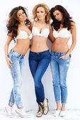 Trio of sexy shapely women in jeans and bras — Stock Photo