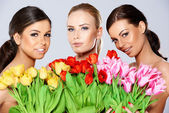 Three beautiful women with fresh spring tulips — Stock Photo