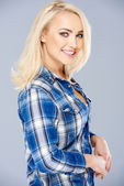 Smiling beautiful blond in a checked blue shirt — Stock Photo