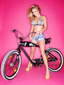 Seductive young blond on a bicycle — Stock Photo