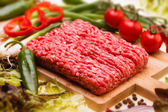 Raw minced meat with vegetables on wooden board — Stock Photo