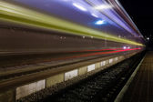 Red and blue train leaving a small roofless dutch train station — Stock Photo