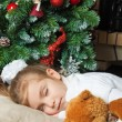 Little girl sleeping with teddy bear near christmas tree — Stock Photo
