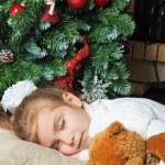 Little girl sleeping with teddy bear near christmas tree — Stock Photo
