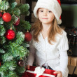 Stock Photo: Little girl in Santa hat with gift near christmas tree