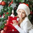 Happy little girl in Santa hat with gifts — Stock Photo