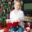 Little girl with gifts near christmas tree — Stock Photo