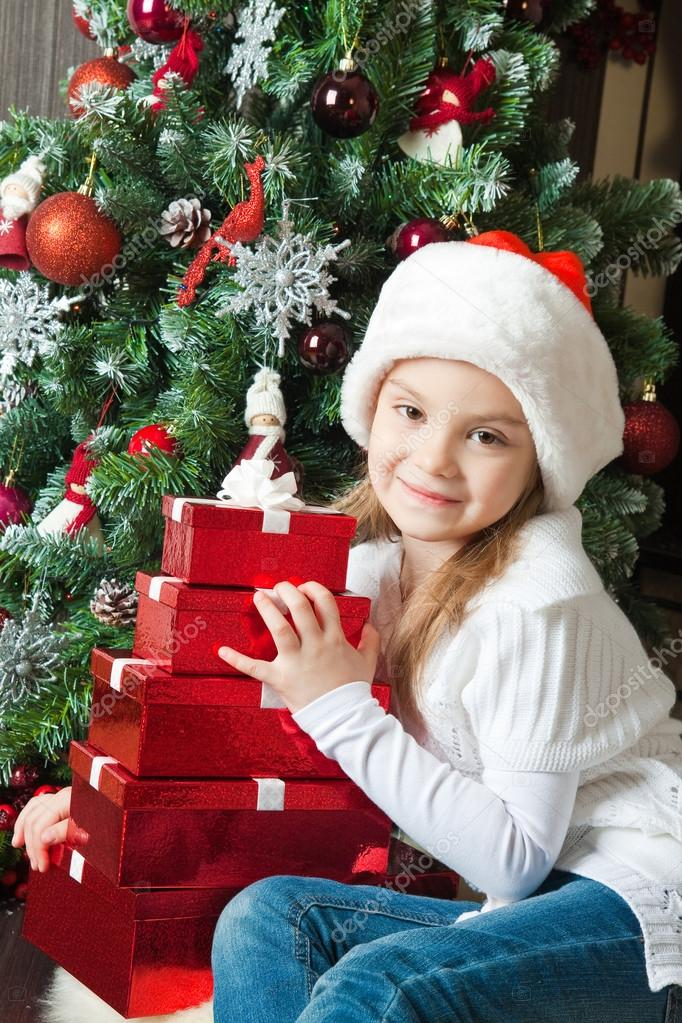 Little girl in Santa hat with gifts near christmas tree — Stock Photo #14354775