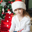 Funny girl in Santa hat writes letter to Santa — Stock Photo #14597107