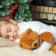 Little girl sleeping and hugging her teddy bear near christmas t — Stock Photo