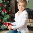 Happy little girl with gifts near christmas tree and fireplace — Stockfoto