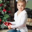 Happy little girl with gifts near christmas tree and fireplace — 图库照片