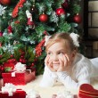 Pretty girl with gift dreaming near christmas tree — Stock Photo