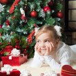 Pretty girl with gift dreaming near christmas tree — Stock Photo #14597221
