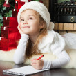Pretty girl in Santa hat writes letter to Santa — Stock Photo