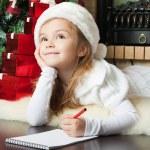Pretty girl in Santa hat writes letter to Santa — Stock Photo