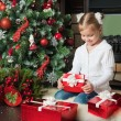 Happy little girl open a red gift box near christmas tree — Foto de Stock