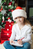 Funny girl in Santa hat writes letter to Santa — Stock Photo