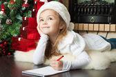 Hübsches mädchen in nikolausmütze schreibt brief an den weihnachtsmann — Stockfoto