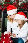 Dívka a matku v santa klobouky napsat dopis do santa — Stock fotografie
