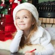 Funny girl in Santa hat writes letter to Santa — Stock Photo #15728873