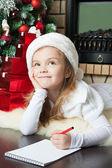 Funny girl in Santa hat writes letter to Santa — Stock Photo