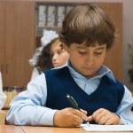 The boy in a dark blue waistcoat writes — Stock Photo #2640102