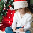 Stock Photo: Girl in Santa hat sits and writes letter to Santa
