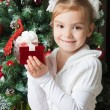 Happy girl in white jacket with gift near christmas tree — Stock Photo