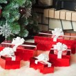 Red gift boxes near christmas tree and fireplace — Stock Photo