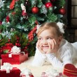 Stock Photo: Happy girl with giftslying near christmas tree