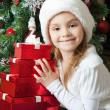 Smiling little girl in Santa hat with gifts — Lizenzfreies Foto