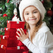 Smiling little girl in Santa hat with gifts — Stock Photo