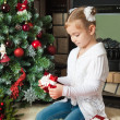 Girl with gifts near christmas tree and fireplace — Stok fotoğraf