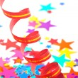Multicoloured confetti stars and red streamer — Stock Photo