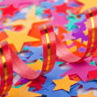 Multicoloured confetti stars and streamer — Stock Photo
