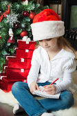 Girl in Santa hat sits and writes letter to Santa — Stock Photo