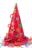 Red party hat with multicoloured confetti stars and streamer — Stock Photo