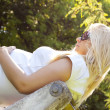 Pregnant woman relaxing in the park — Stock Photo #29983113