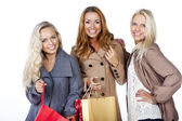 Group of happy smiling women shopping with colored bags — Stock Photo