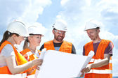 Engineer builders examining blueprint at construction site — Stock Photo
