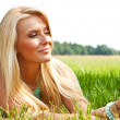 Stock fotografie: Woman relaxing outdoors looking happy and smiling